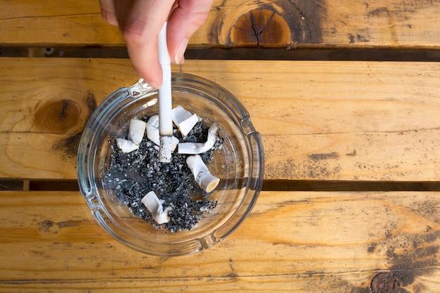 Vrouw die een sigaret rookt die een brandend filteruiteinde in haar hand houdt.