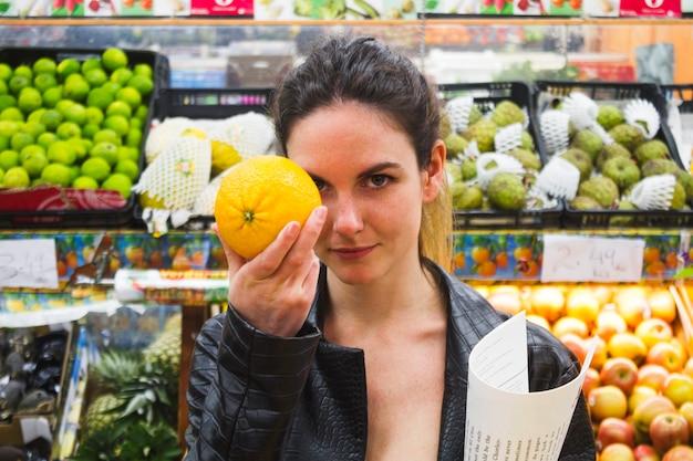 Vrouw die een sinaasappel in een kruidenierswinkelopslag houdt
