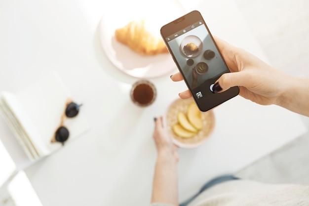 Vrouw die een smartphone gebruikt om een foto van haar maaltijd te maken
