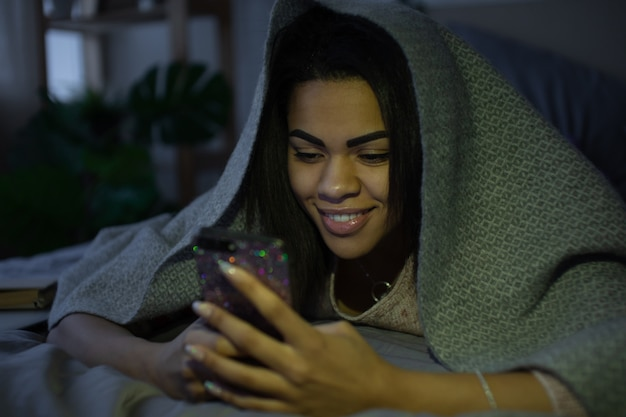 Vrouw die een smartphone in bed gebruiken bij nacht