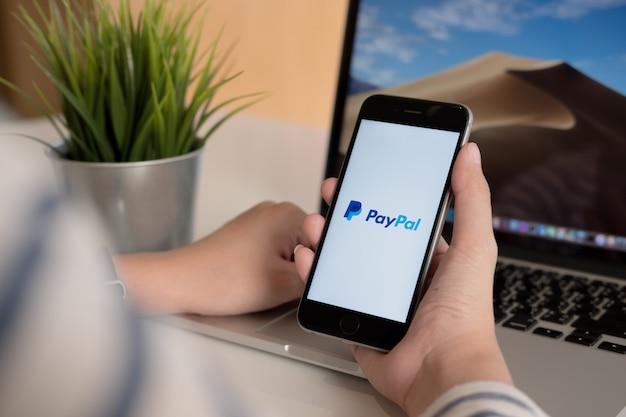 Vrouw die een smartphone met de dienst online betalingen op het scherm houdt.
