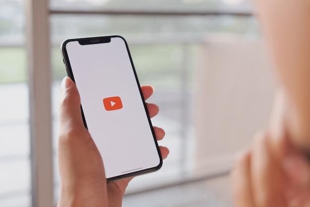 Vrouw die een smartphone met sociale internet-dienst youtube op het scherm houdt
