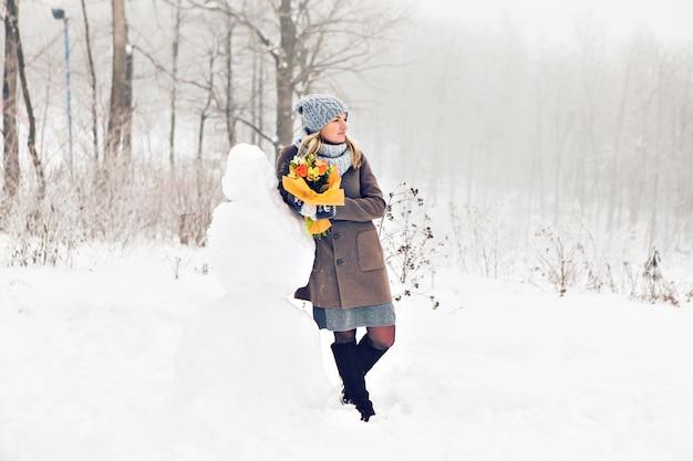 Vrouw die een sneeuwman in wintertijd maakt