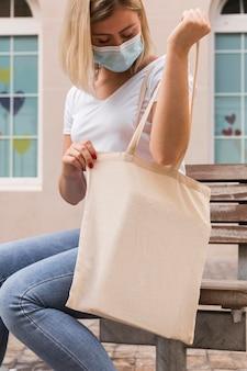 Vrouw die een stoffen zak draagt en erin kijkt
