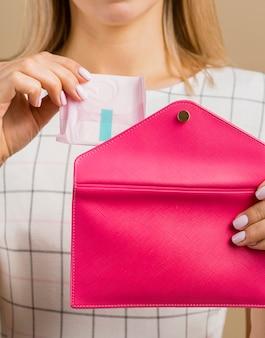 Vrouw die een stootkussen van haar portefeuille toont