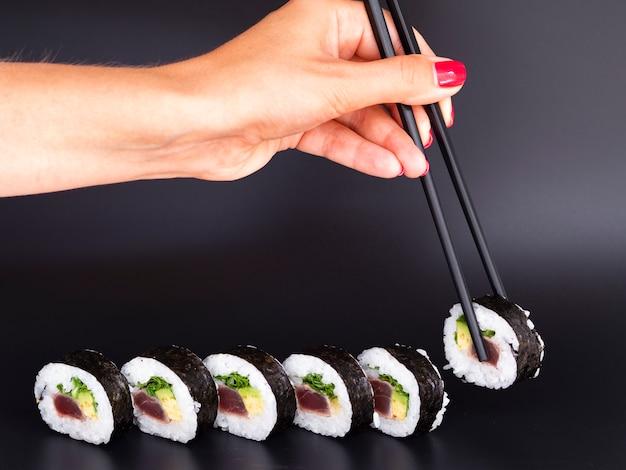 Vrouw die een stuk sushibroodje plukt