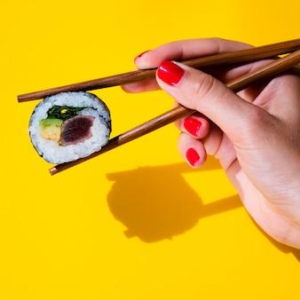 Vrouw die een sushibroodje in eetstokjes op gele achtergrond houdt