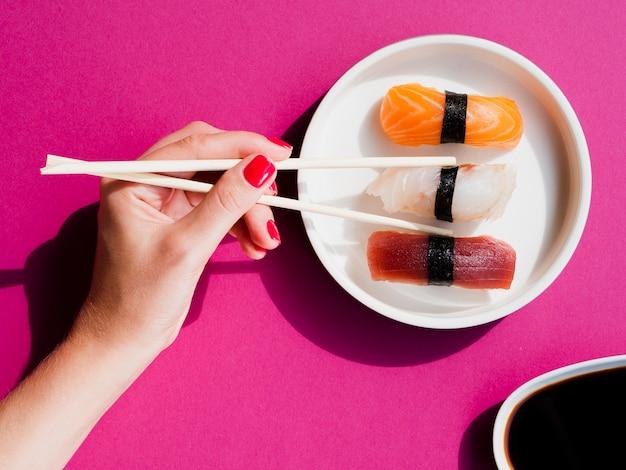 Vrouw die een sushistuk met eetstokjes neemt