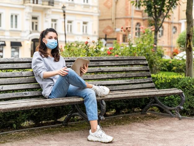 Vrouw die een tablet bekijkt terwijl het dragen van medisch masker met exemplaarruimte