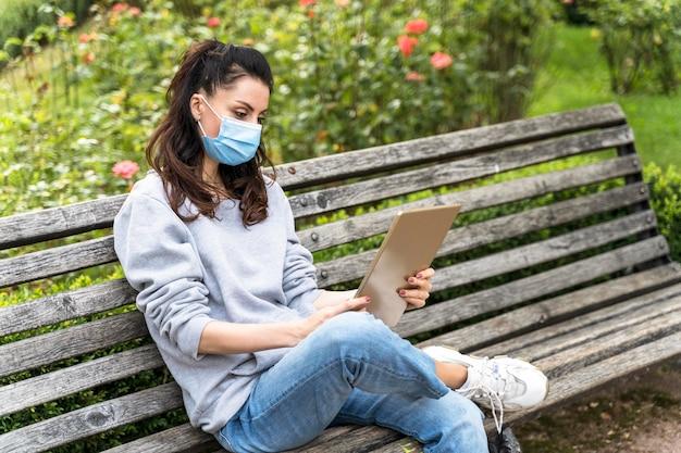 Vrouw die een tablet bekijkt terwijl zij medisch masker draagt