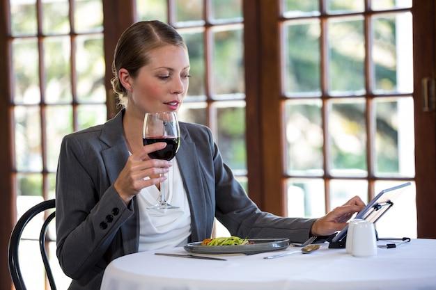 Vrouw die een tablet gebruikt en wijn drinkt