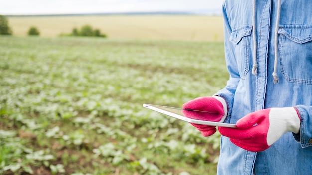 Vrouw die een tablet naast een landbouwbedrijfgebied houdt