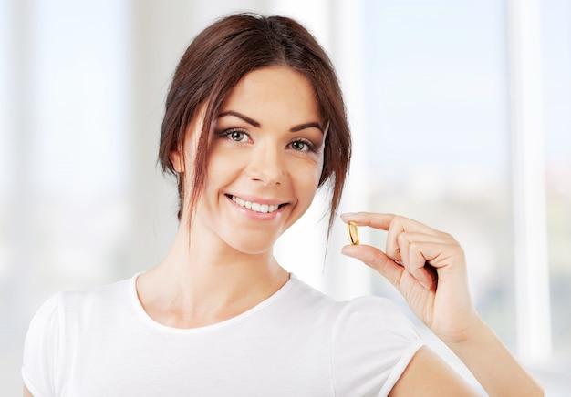 Vrouw die een tablet neemt. close-up hand met een pil en de mond, geïsoleerd op background