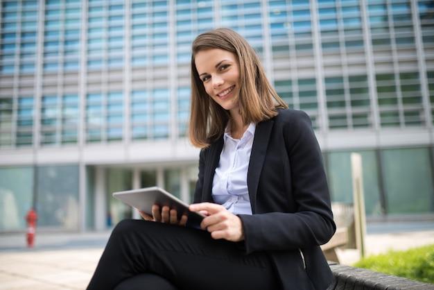 Vrouw die een tablet voor haar bureau gebruikt