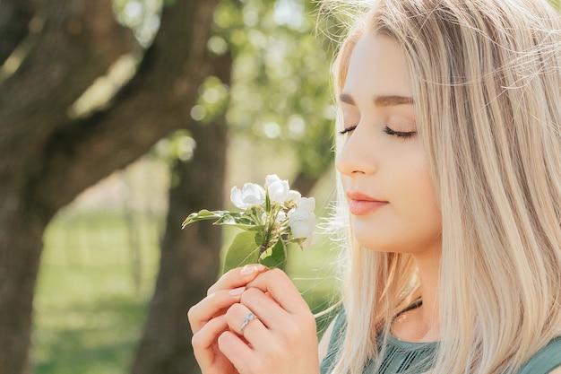 Vrouw die een tak van een bloeiende boom in haar handen houdt en bloemen snuffelt met haar ogen dicht