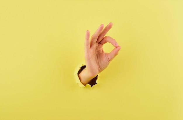 Vrouw die een teken van overeenstemming over gele achtergrondexemplaar ruimteclose-up tonen