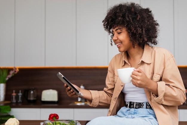 Vrouw die een telefoon en een kop van koffie in keuken houdt