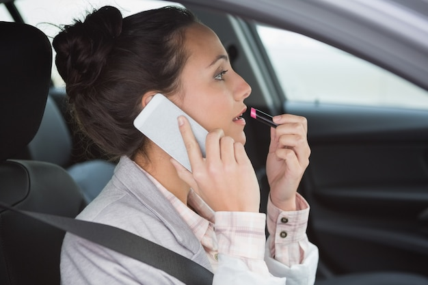Vrouw die een telefoongesprek heeft terwijl het zetten van lippenstift