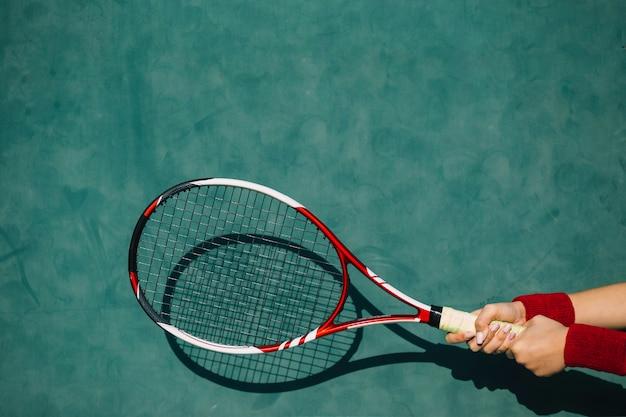 Vrouw die een tennisracket in beide handen houdt