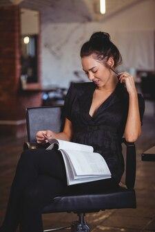 Vrouw die een tijdschrift leest bij de kapsalon