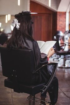 Vrouw die een tijdschrift leest terwijl het wachten met haarverf in haar hoofd