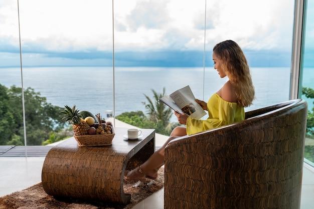 Vrouw die een tijdschrift op een balkon leest