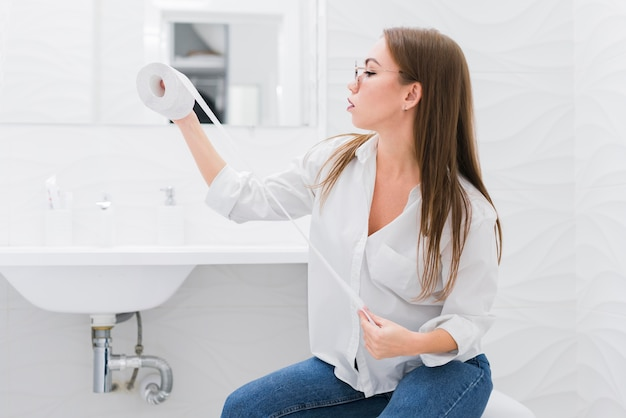 Vrouw die een toiletpapier bekijkt terwijl het zitten op het toilet