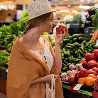 Vrouw die een tomaat ruikt