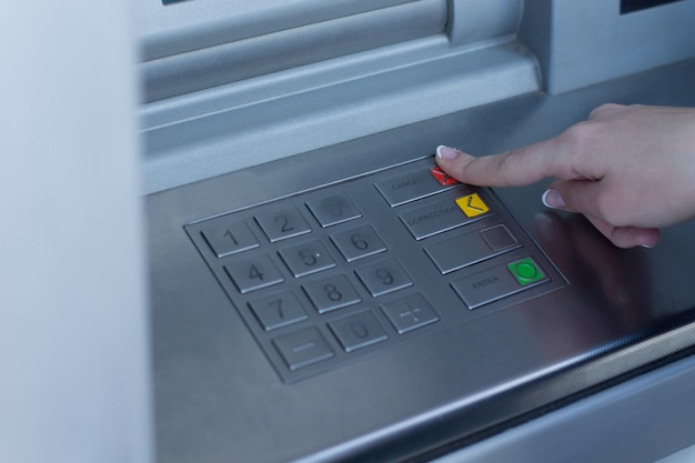 Vrouw die een transactietype selecteert op de bank atm door met haar vinger op de rode knop te drukken terwijl ze de validatie van haar identificatie en pincode voltooit
