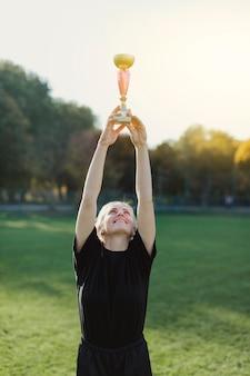 Vrouw die een trofee boven haar hoofd opheft