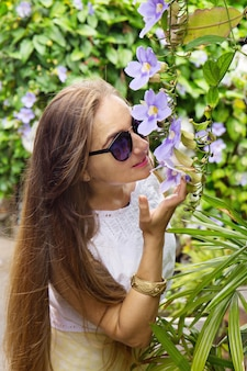 Vrouw die een tropische bloem snuift