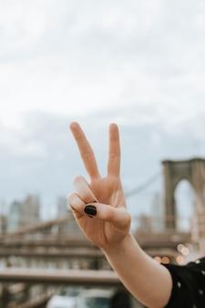 Vrouw die een v-teken toont bij de brug van brooklyn, de vs