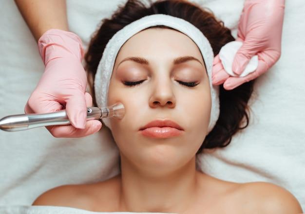 Vrouw die een vacuüm gezichtsmassage in kosmetische kliniek ontvangt