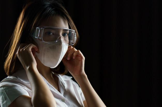 Vrouw die een veiligheidsbril en masker draagt, om de verspreiding van coronavirus te voorkomen.