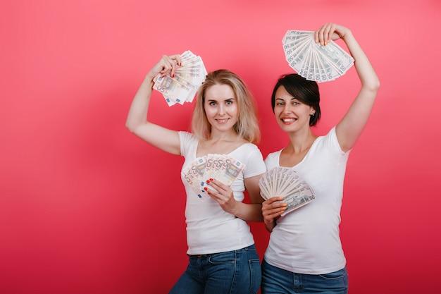 Vrouw die een ventilator van geld in beide handen houdt en gelukkig kijkt.