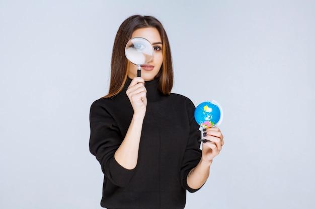 Vrouw die een vergrootglas houdt en de wereldbol controleert.