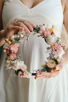 Vrouw die een verlovingsring draagt met een bloemenkrans gemaakt met exotische bloemen