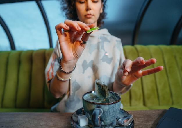 Vrouw die een verse mok thee met theezakje in koffie brouwen