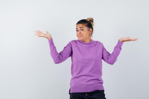 Vrouw die een verwelkomend gebaar in wollen blouse toont en er zelfverzekerd uitziet Gratis Foto