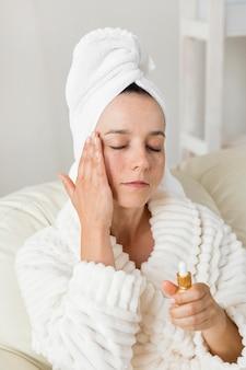 Vrouw die een vochtinbrengende crème voor haar huid gebruikt en een badjas draagt
