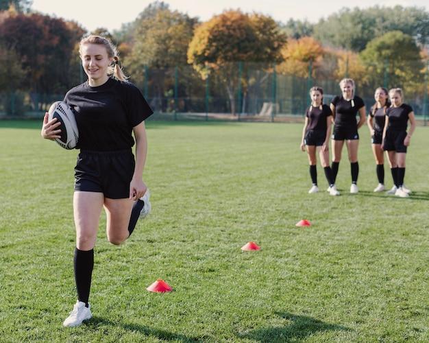 Vrouw die een voetbalbal houdt en kegels doorneemt
