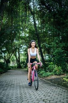 Vrouw die een wegfiets in het park berijdt. portret van jonge mooie vrouw op roze fiets.
