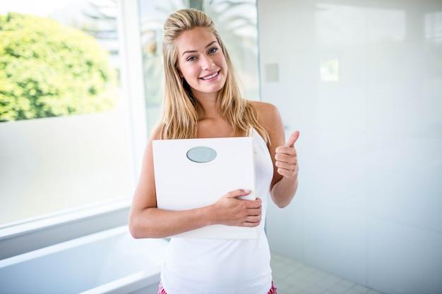 Vrouw die een wegingsschaal met duimen in de badkamers omhoog houdt
