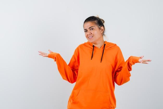 Vrouw die een welkomstgebaar in oranje hoodie toont en er vrolijk uitziet