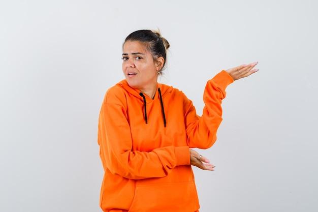 Vrouw die een welkomstgebaar in oranje hoodie toont en er zelfverzekerd uitziet