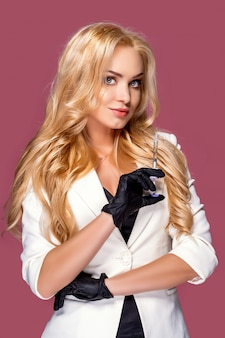 Vrouw die een wit jasje draagt dat een spuit houdt