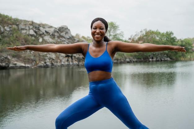 Vrouw die een yoga-pose buiten onderwijst