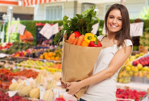 Vrouw die een zak in een fruit en een plantaardige openluchtmarkt houdt