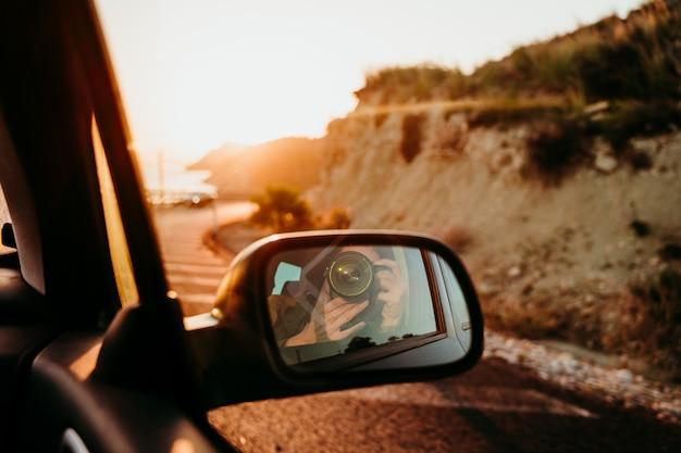 Vrouw die een zelfportret in achteruitkijkspiegel in een auto nemen bij zonsondergang. reis concept