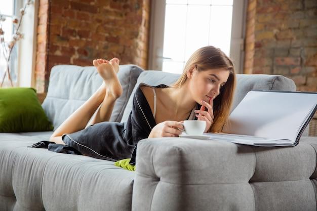 Vrouw die een zijden gewaad draagt die haar dagelijkse huidverzorgingsroutine thuis doet.